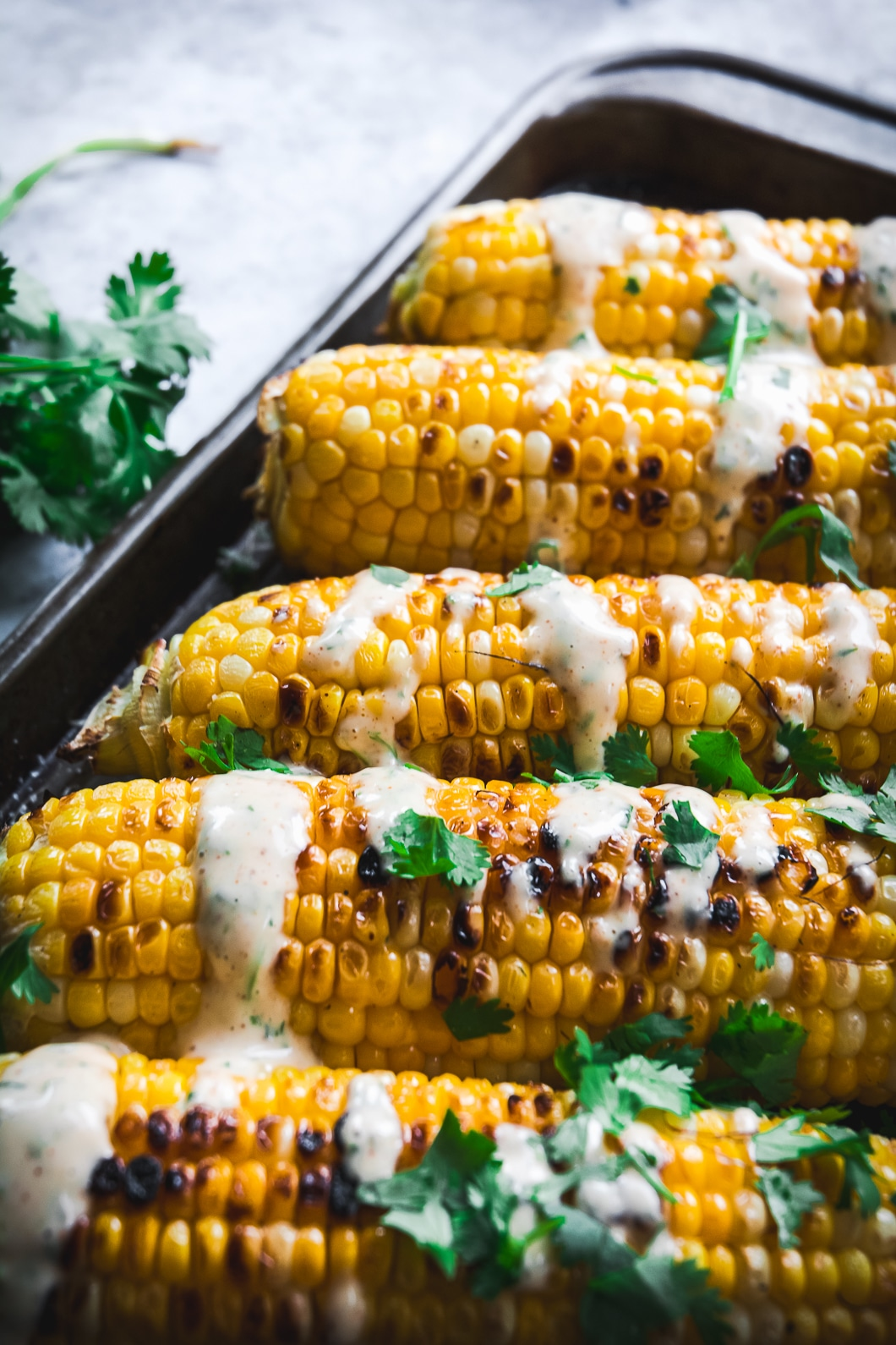 Grilled Corn with Spicy Habanero Honey Mayo up close on tray with cilantro