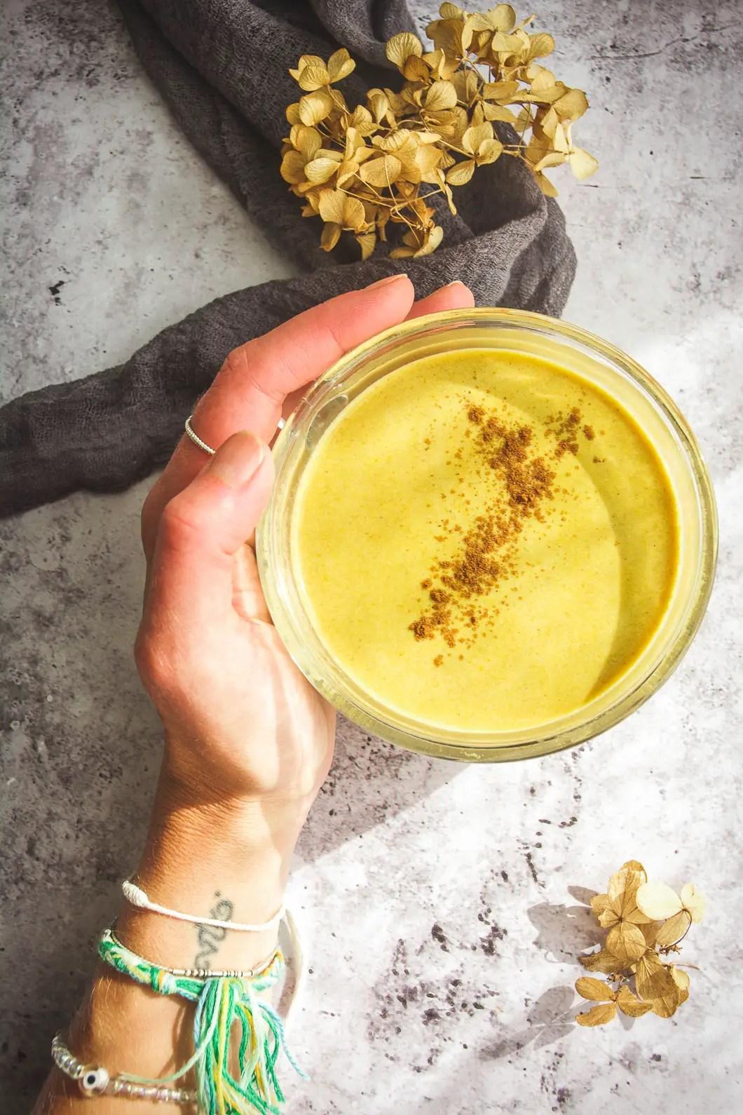 pumpkin spice latte in clear mug held by hand