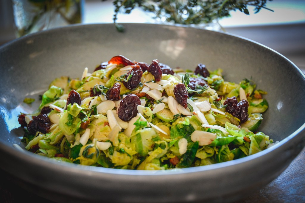 Warm Brussels Sprouts Salad with Bacon and Dried Cherries in grey bowl