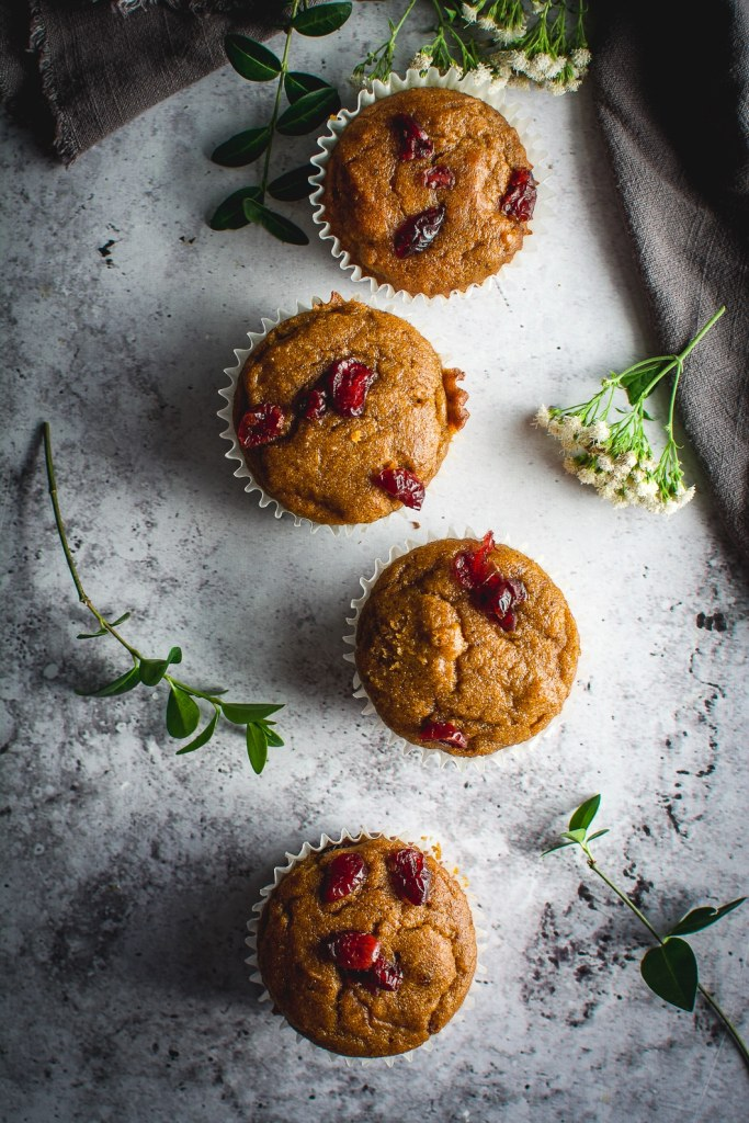 Healthy Grain-Free Cranberry Pumpkin Spice Muffins on table with greens, flowers and napkin