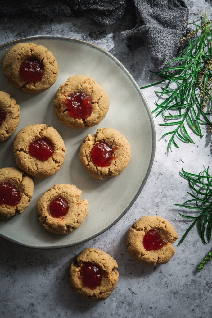 Almond Flour Cardamom Peanut Butter Thumbprint Cookies shot from above on plate and table