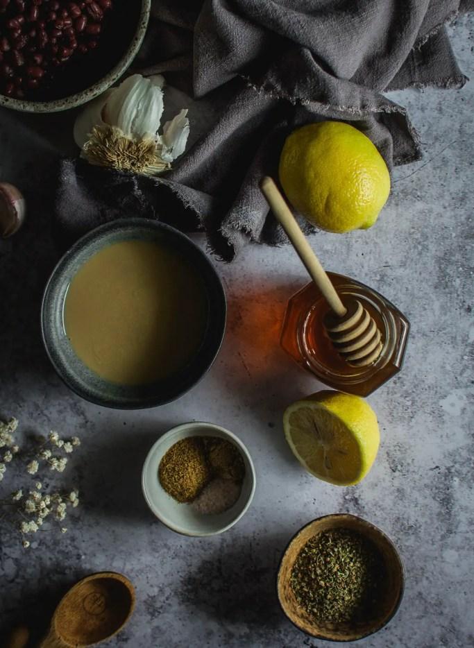 lemons, garlic, tahini, adzuki beans in bowl, honey in jar