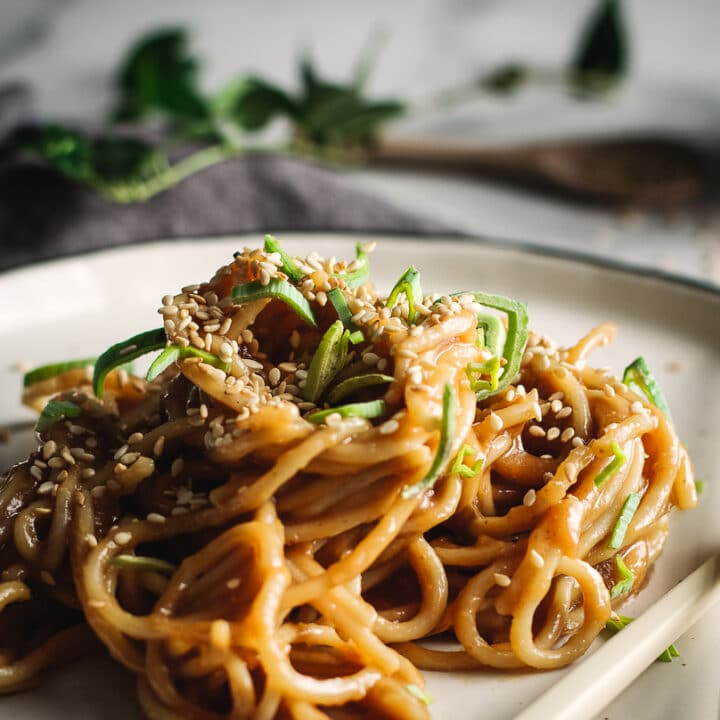 Sesame peanut noodles on plate sprinkled with sesame seeds and sliced green onion