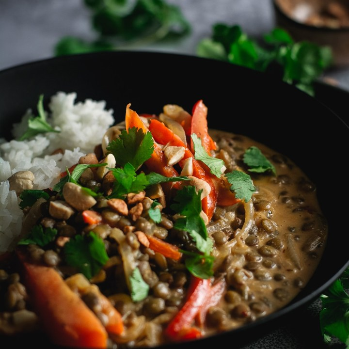 Peanut Lentil Curry in black bowl with red pepper rice, cilantro and crushed peanuts