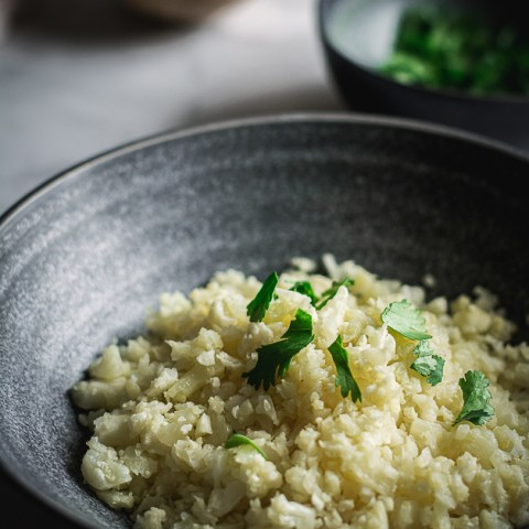cauliflower rice in bowl with cilantro leaves