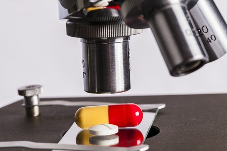 Image showing a microscope focused on a red and orange capsule and a white pill, depicting the different phases of clinical trials, as described in this article on CALMERme.com