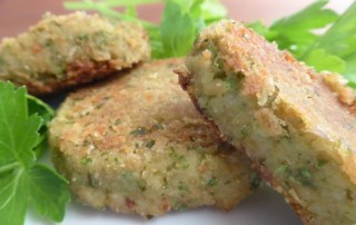 Image of falafel patties on a bed of cilantro and parsley, showing the falafel's filling of cilantro and chick pea as well as the crispy outside coating, as described in this recipe on CALMEme.com
