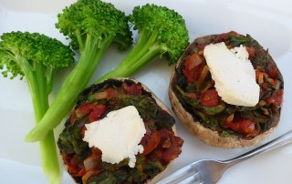 Image shows portobello mushroom stuffed with tomatoes, leafy greens, and onion with a side of broccoli, as described in this recipe on CALMERme.com