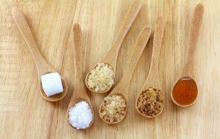 Image of spoons of different sweeteners, relating to CALMERme blog post on the effect of sweeteners on cancer