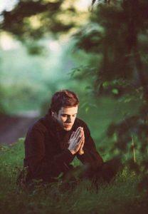 Joven meditando en un bosque