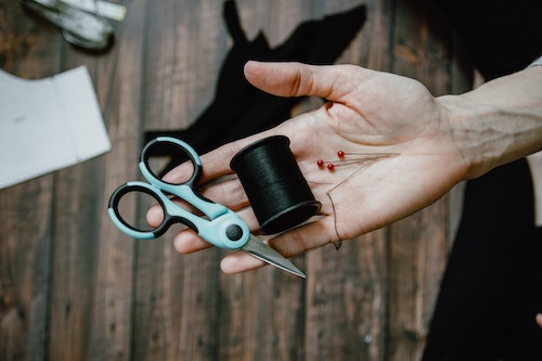 Woman holding scissors, pins, and sewing thread. Harm OCD can make people fear they will harm loved ones with seemingly common objects.