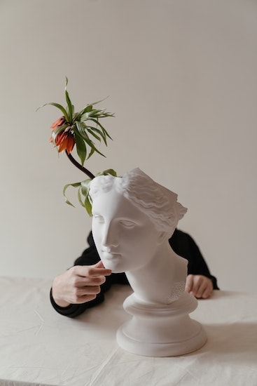Man hiding behind a marble bust. Panic attacks can often bring about a sense of disconnection with one's body and feeling out of touch with reality, known as depersonalization or derealization. Get OCD treatment in California or online OCD counseling in Montana here.
