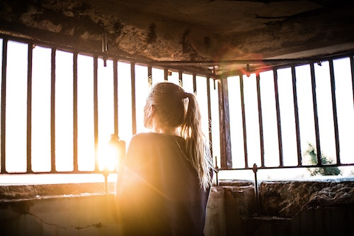 Woman looking out from behind bars. Panic attacks can make you feel trapped inside your own body. Get panic disorder treatment in California or online panic attack  counseling in Montana here.