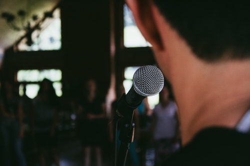 Man looking at an audience with a microphone in front of him. Speaking in public is a common fear that can impact someone's career and social life. Get OCD treatment in California or online OCD counseling in Montana here.