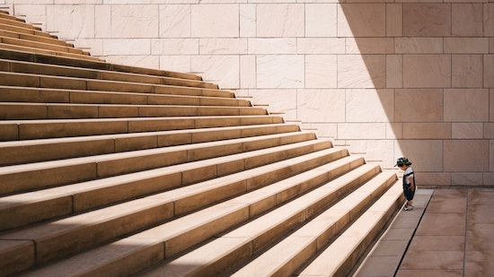 Little boy contemplating walking up a large flight of stairs. Cognitive Behavioral Therapy can feel overwhelming, but progress is done step by step, not all at once. Get OCD treatment in California or online OCD counseling in Montana here.