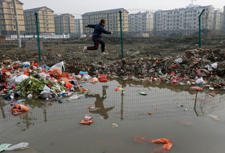A boy jumps over heaps of trash in Jiaxing. Unsanitary conditions are a serious health problem in China.