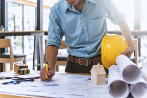 A man in a rolled up button down and jeans holding a yellow hard hat using a pen to make changes on a blueprint with several rolled up blueprints on his left.
