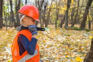 A small boy carries a wrench over his shoulder and wears orange hardhat and safety vest.