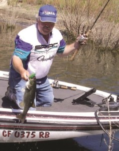 Kelly Salmons with a fresh-caught fish in his boat.