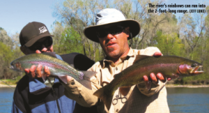 two men, one holding two rainbow trout.