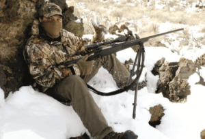 Young man in full winter hunting gear with rifle, sitting in the snow.
