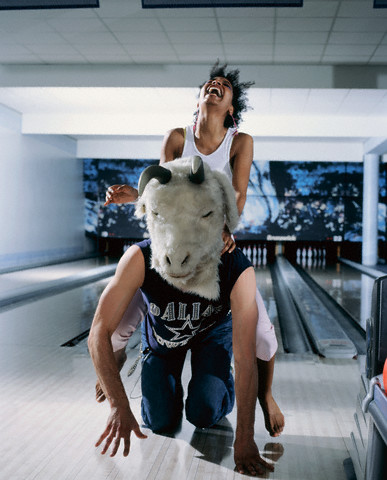 Young Woman Riding Man in Goat Mask in Bowling Alley --- Image by © Rainer Holz/zefa/Corbis
