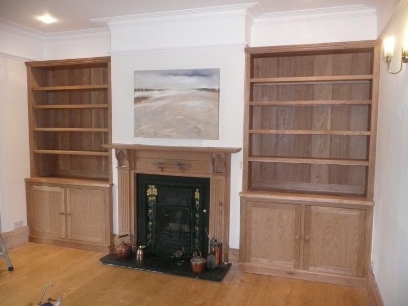 Pair of Oak bookcases precisely fitted to alcoves on both sides of fireplace