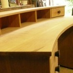 Curved desk with integrated file cabinet and partitioned drawers