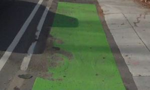 Bicycle marking under green paint at bus stop on Concord Avenue