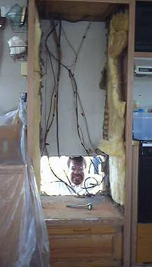 Brent sticks his head in through the hole for the refridgerator
