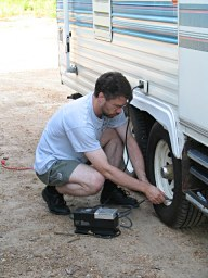 Brent fills the trailer tires with air as we prepare to travel again, photograph by Lorelle VanFossen