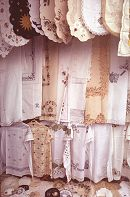lace edged table cloths hanging from a store front are popular in Greece, Rhodes, photograph by Lorelle VanFossen