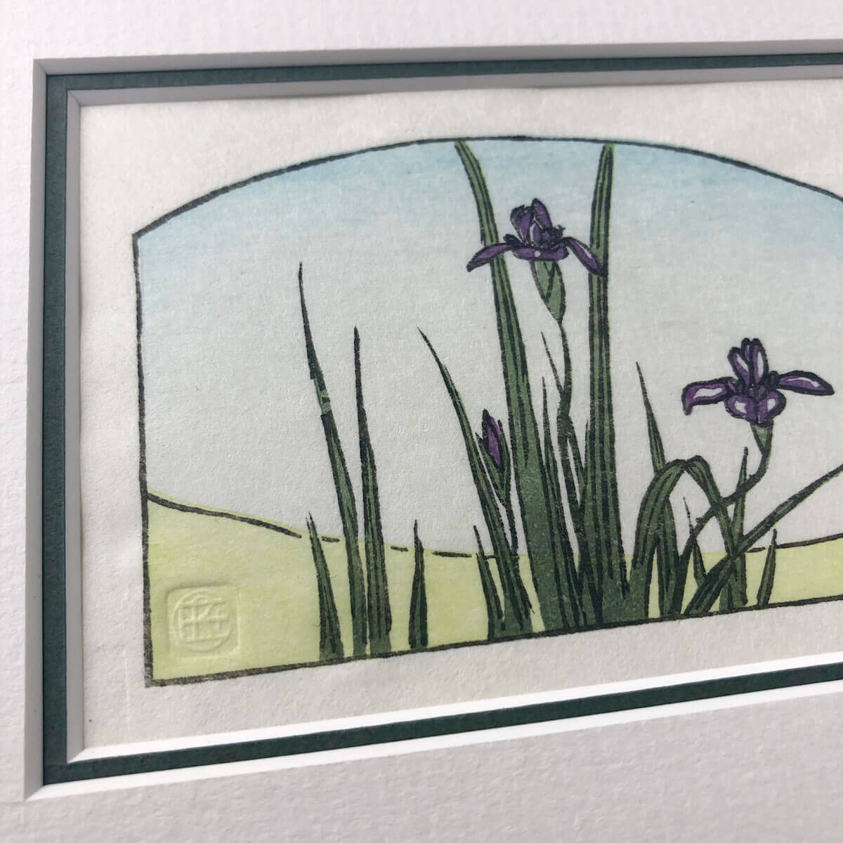 handmade woodblock print of purple iris flowers and foliage with green ground and pale blue sky
