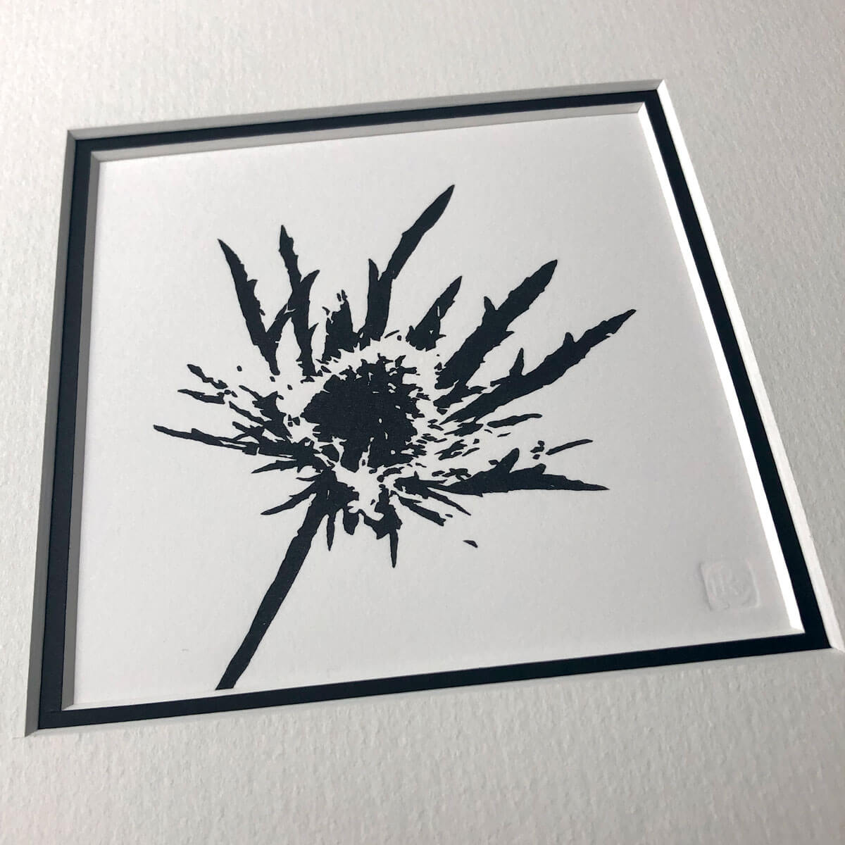 handmade woodblock print of a sea holly flowerhead in pure black against plain pale background