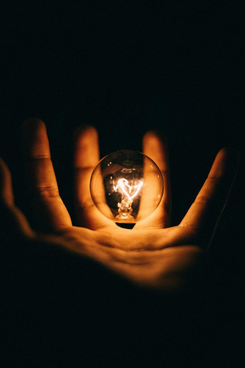 A hand holding a lit lightbulb on a dark backdrop