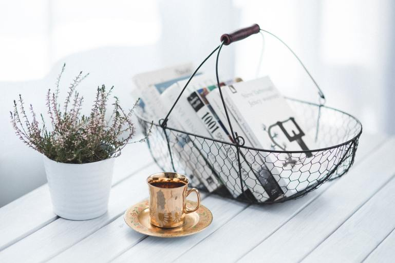Basket of books, plant, and cup of coffee