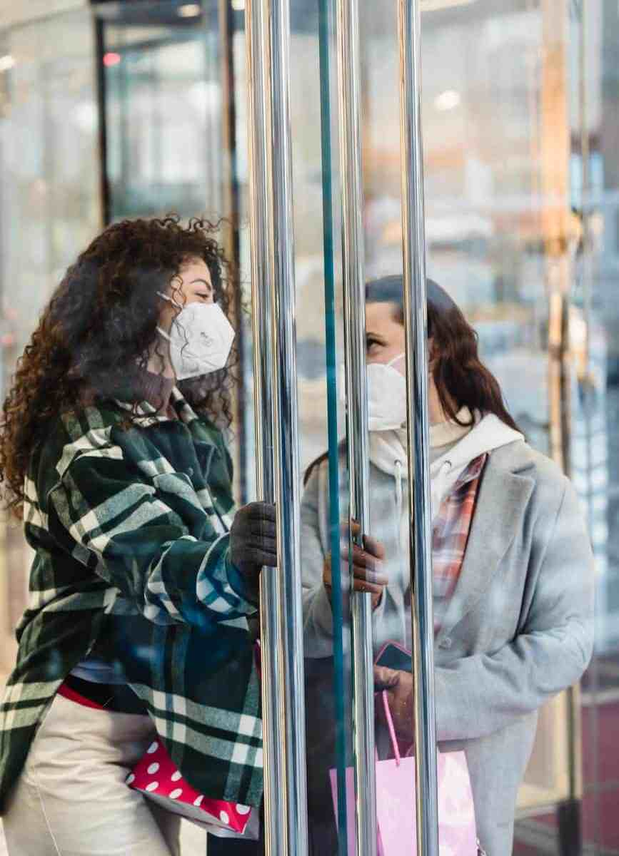 content diverse women in medical mask standing near store