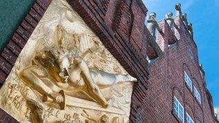 """Das vergoldete Bronzerelief """"Lichbringer"""" stammt ebenfalls von Bernhard Hoetger, der auch in Worpswede tätig war. Es hängt über dem Portal zur Böttcherstraße. Sonnabends um 11:30 Uhr beginnt dort eine öffentliche Führung durch die Gasse."""