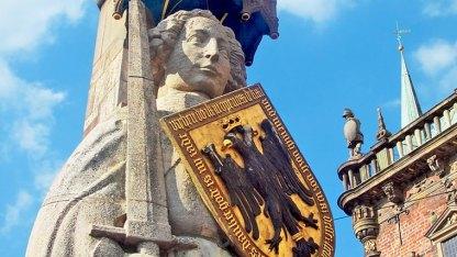 Seit 1404 steht der fünfeinhalb Meter große Bremer Roland vor dem Rathaus und schaut in Richtung Dom. Sein Schild trägt das Wappen des Kaisers. Rathaus und Roland gehören zum UNESCO-Weltkulturerbe.