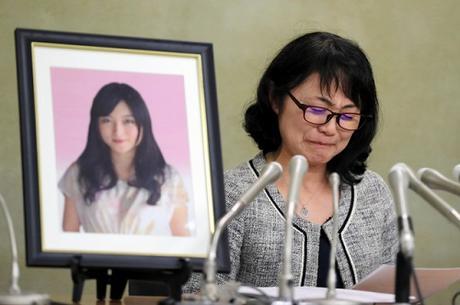 Mẹ của Matsuri Takahashi khóc trước di ảnh con gái. Ảnh: Japan Times