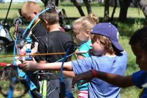 boys shooting bows and arrows