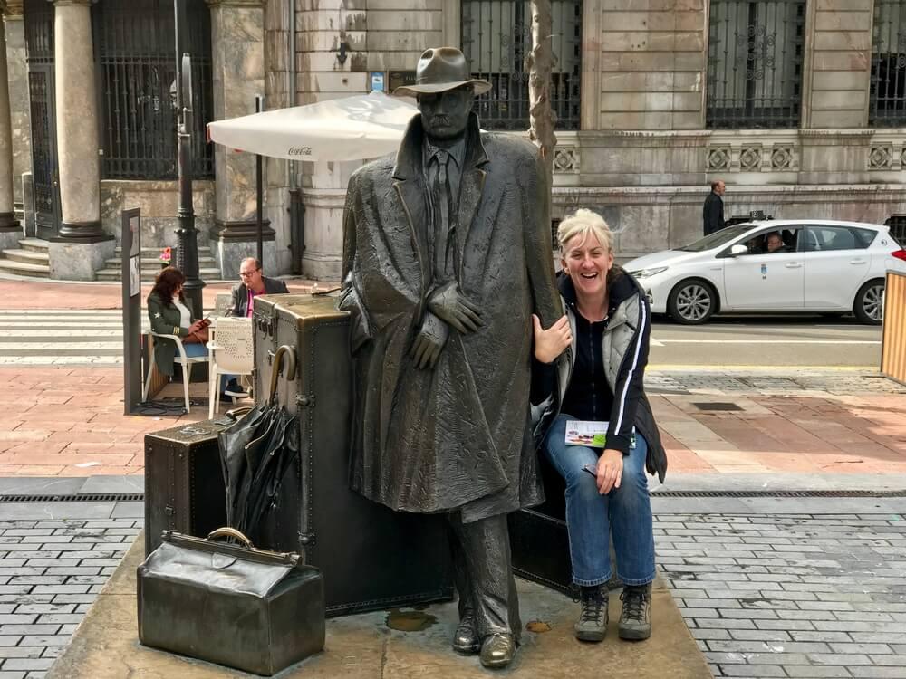 Janine houdt het beeld van de Viajero in Oviedo vast. Het beeld is een ode aan de reiziger. Ze houdt Spaanse CP-lijstjes bij.