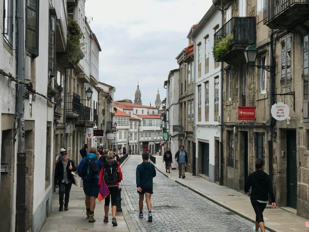 De laatste loodjes voor de bedevaartgangers op de Rúa de San Pedro met de torens van de kathedraal in zicht.