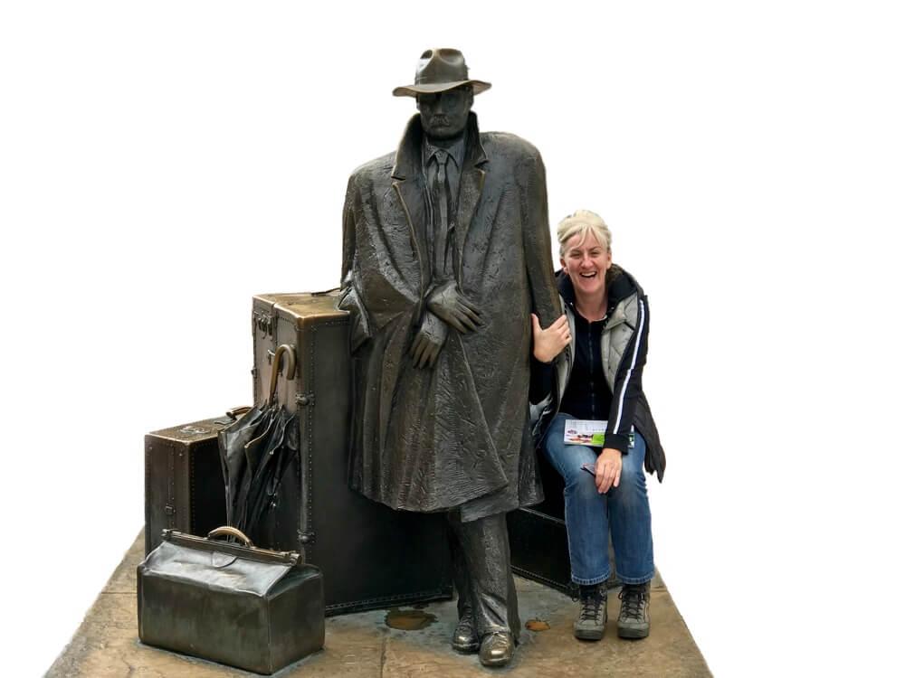 Janine houdt het beeld van de Viajero in Oviedo vast. Het beeld is een ode aan de reiziger.