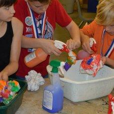 Kiddos spraying their shirts in buckets.