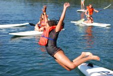 Camper jumping off of paddleboard