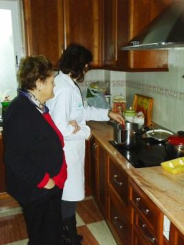 Una cuidadora ayuda a una persona mayor a preparar la comida.