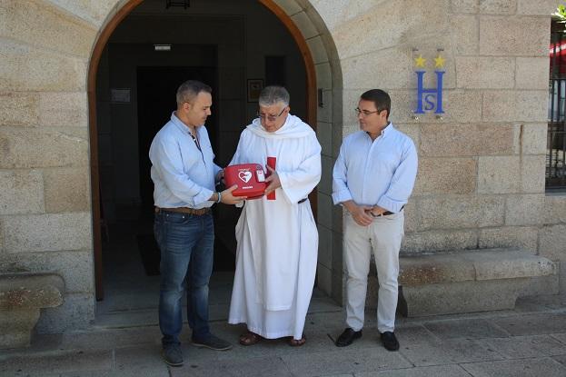 Jesús del Moral y Pedro Luis Rodríguez hacen entrega del desfibrilador al padre Domingo Conesa.