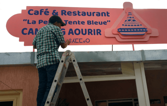 Rashid putting the letters on the restaurant billboard on our campsite