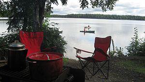 Camp kitchen, folding camping chairs, kayaks on lake -...